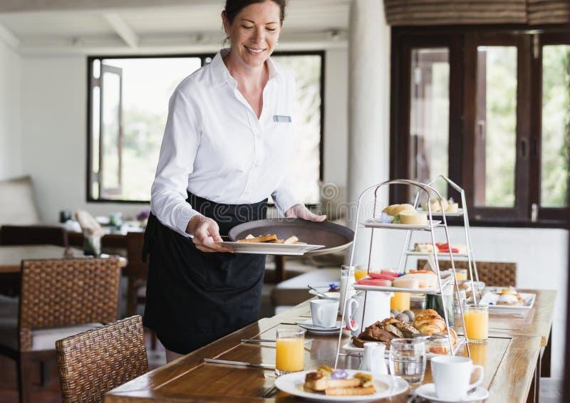 旅馆女服务员在桌上的服务食物 库存照片