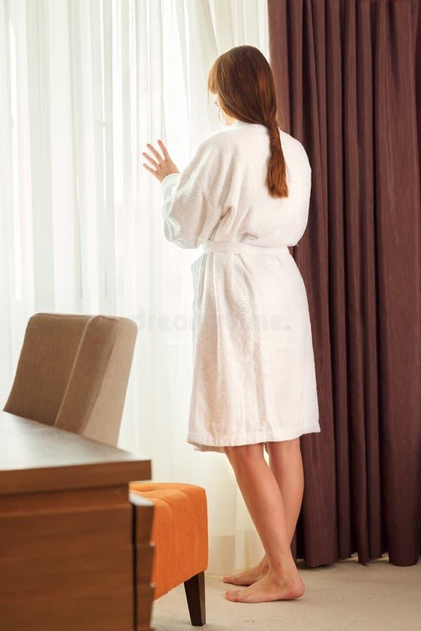 旅馆客房饮用水的少妇 免版税库存照片