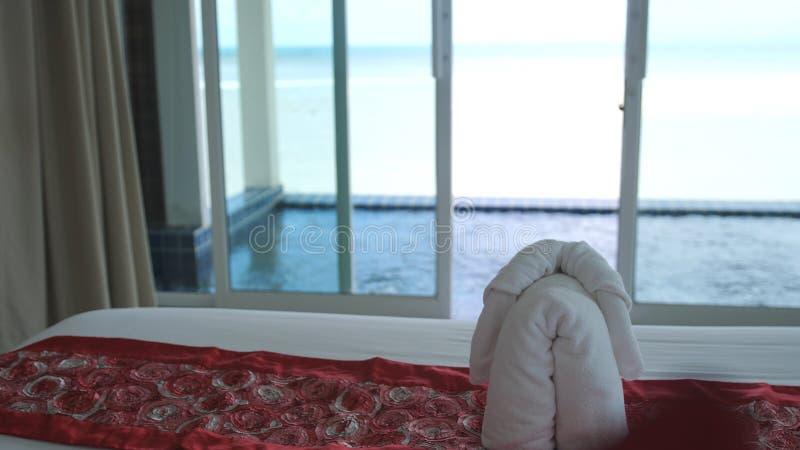 旅馆床在有白色卧具的豪华旅馆室 在极可意浴缸的受欢迎的手段装饰和前景的海 毛巾是 库存图片