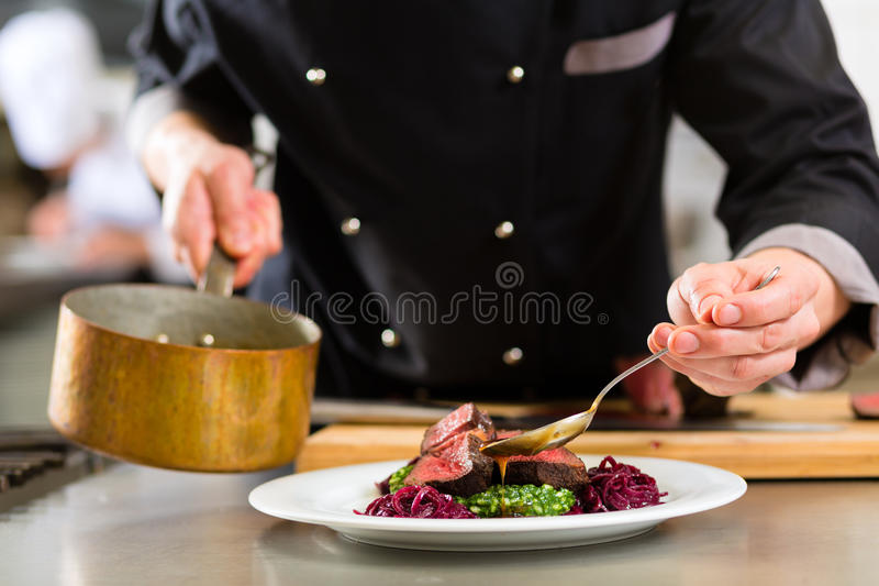 旅馆或餐馆厨房烹调的厨师 免版税库存图片