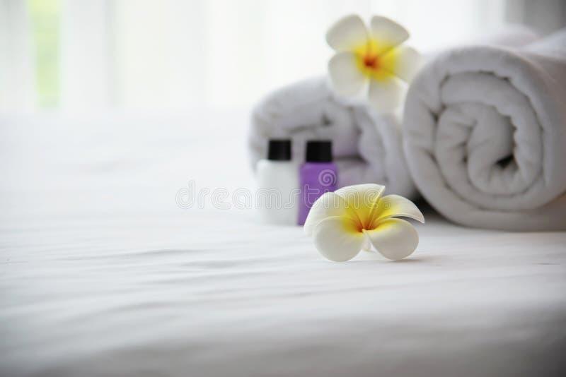 旅馆毛巾和香波和肥皂设置在与羽毛花的白色床上装饰的浴瓶 免版税库存照片