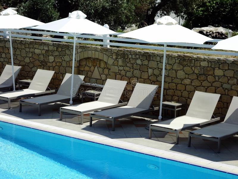 旅馆游泳池、太阳床和伞 免版税图库摄影