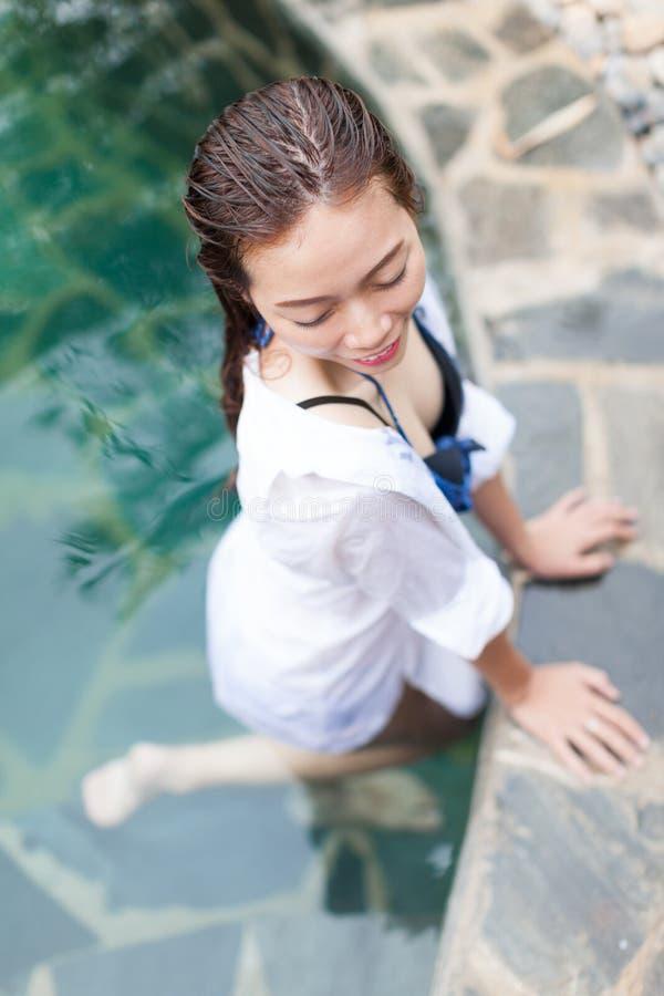 旅馆游泳池松弛假期旅行的亚裔妇女,享用温泉的女孩 免版税库存图片
