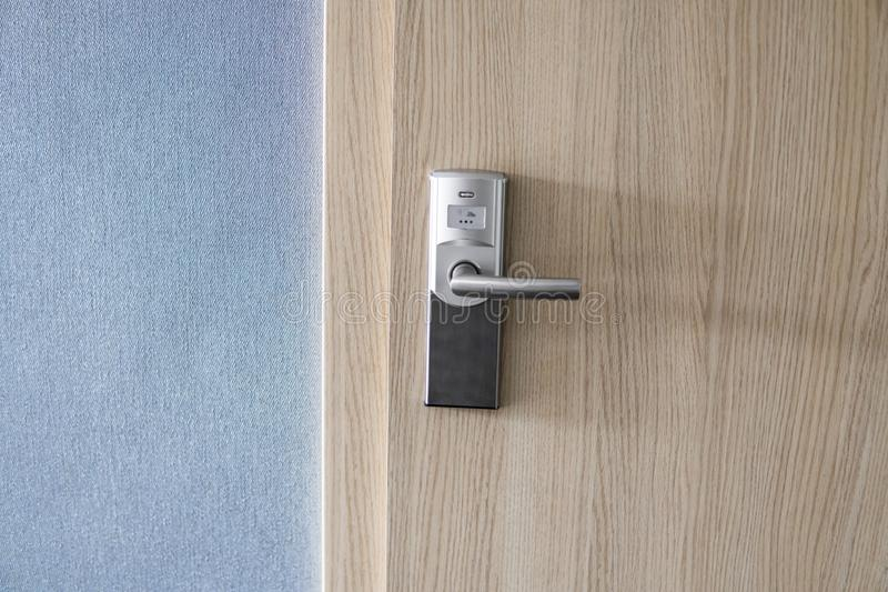 旅馆电子锁在木门和有蓝色墙壁的 库存照片