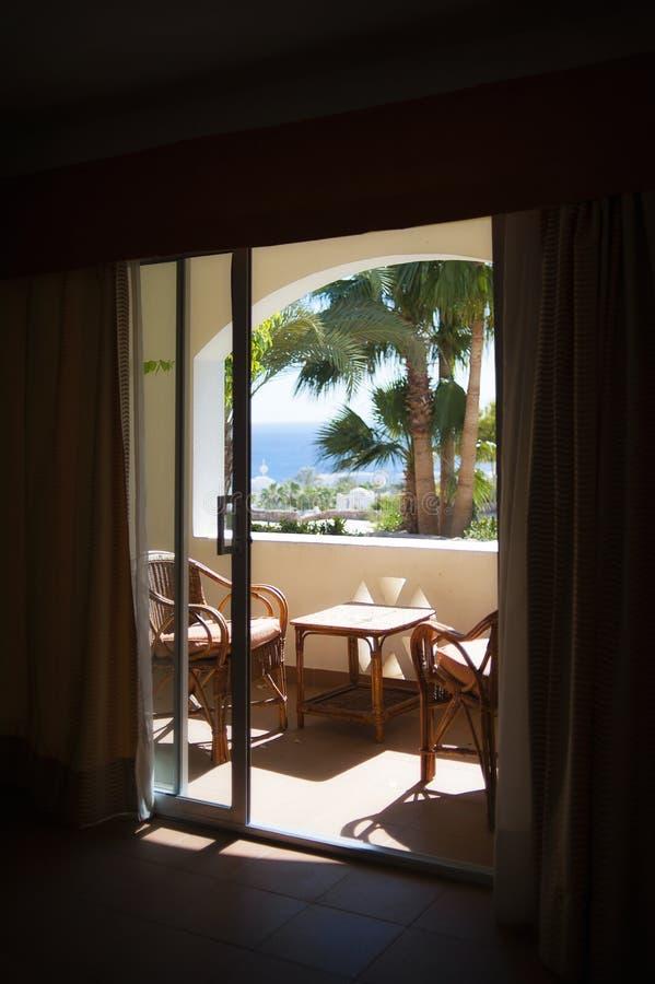 从旅馆窗口的看法在海和棕榈tre 免版税图库摄影
