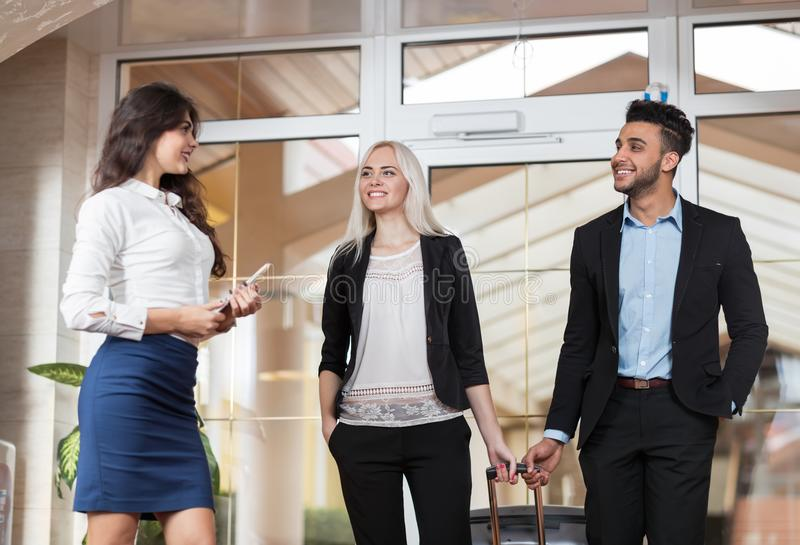 旅馆管理员欢迎在大厅、买卖人小组人和妇女客人的企业夫妇到达 免版税库存图片