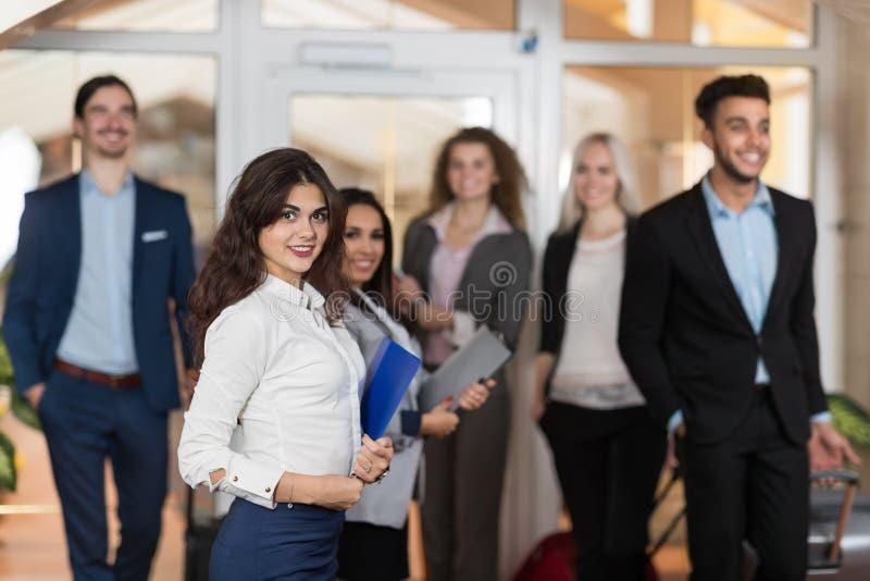 旅馆管理员欢迎大厅的商人,混合种族买卖人小组客人到达 免版税图库摄影