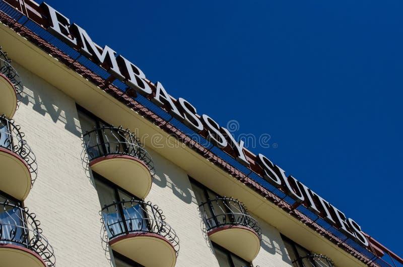 旅馆- Embassy Suites反对一明亮的天空蔚蓝的旅馆标志,这是与地点的美国连锁旅馆 免版税库存图片