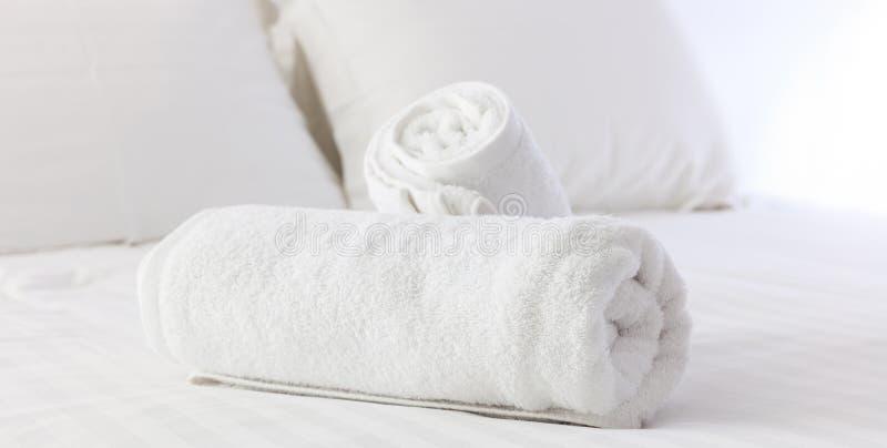 旅馆` s卧室 白色蓬松,滚动的毛巾,亚麻制板料和枕头在床上 关闭视图 库存照片