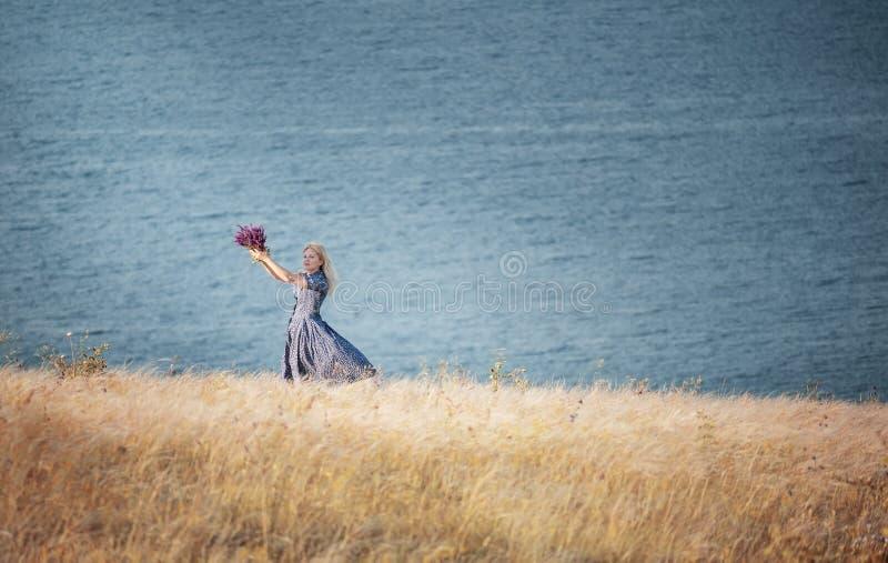 旋转与野花花束的女孩在她的手上在峭壁的草中由海 幸福大气和 免版税库存图片
