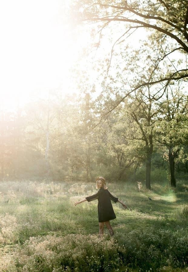 旋转在一串足迹的草帽的时髦的女孩在森林里 免版税库存图片