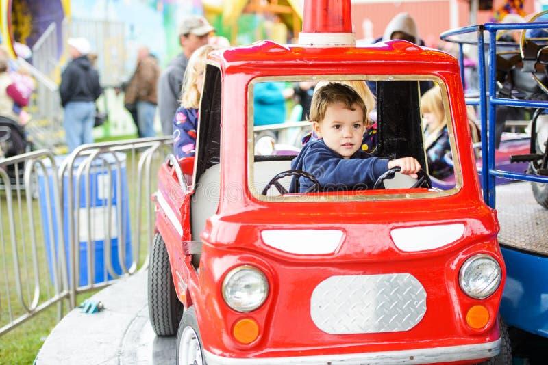 旋转木马救火车的男孩 免版税图库摄影