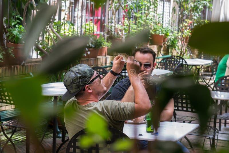 无固定职业的摄影师交换非法钱财的射击了两个人 免版税库存照片