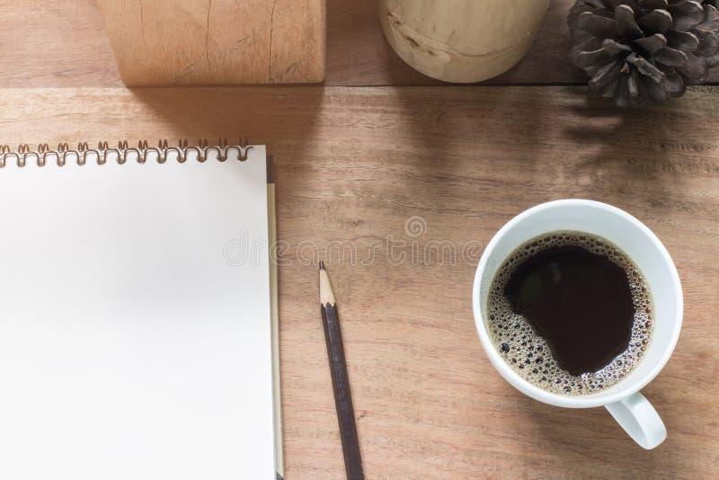 无奶咖啡杯子和笔记本在木书桌上 库存图片