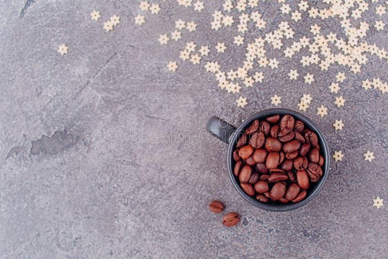 无奶咖啡芬芳五谷在一块黑玻璃的在灰色具体背景 库存照片