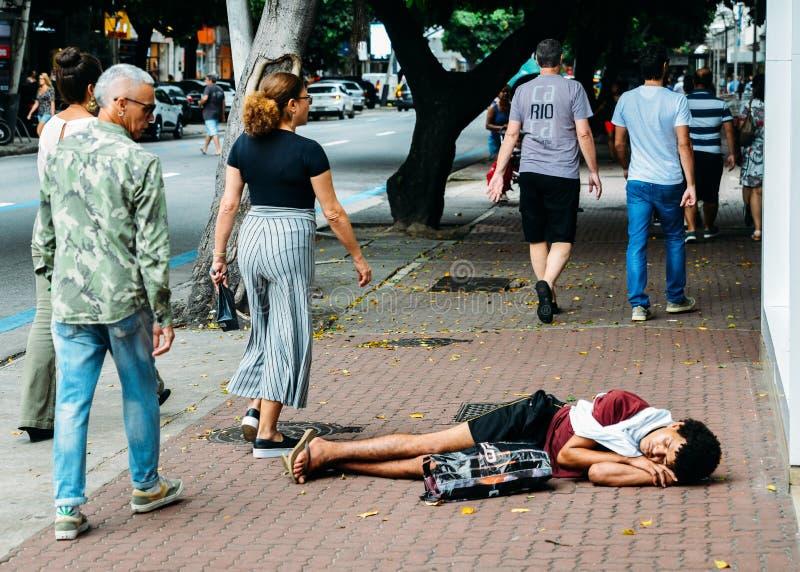 无家可归年轻人睡觉粗砺在边路在里约热内卢,巴西 免版税库存图片