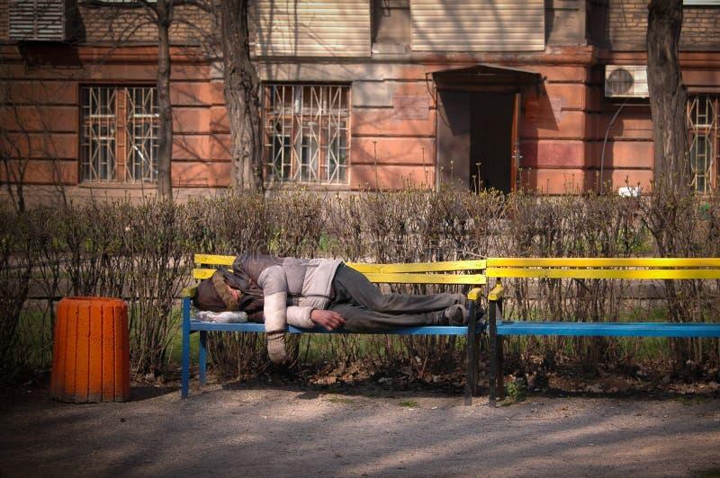 无家可归的人在长凳睡觉 免版税库存图片