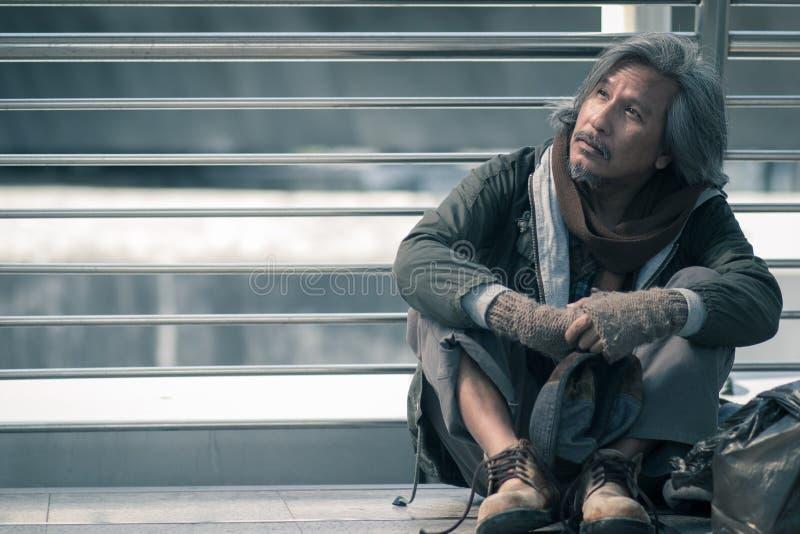 无家可归的人坐走道街道在城市 他从仁慈人的等待的帮助 免版税库存照片