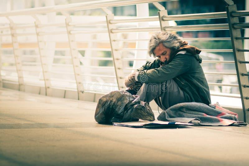 无家可归的人坐走道街道在城市 他睡觉并且需要从仁慈人的帮助 免版税库存照片