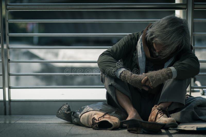 无家可归的人坐走道街道在城市 他睡觉并且需要从仁慈人的帮助 库存照片