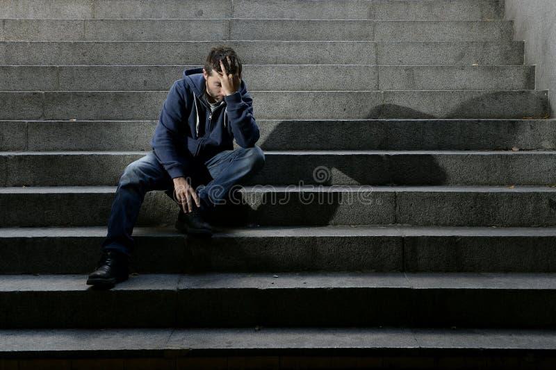 年轻无家可归的人失去了在危机遭受的消沉的工作坐地面街道混凝土台阶 免版税库存照片