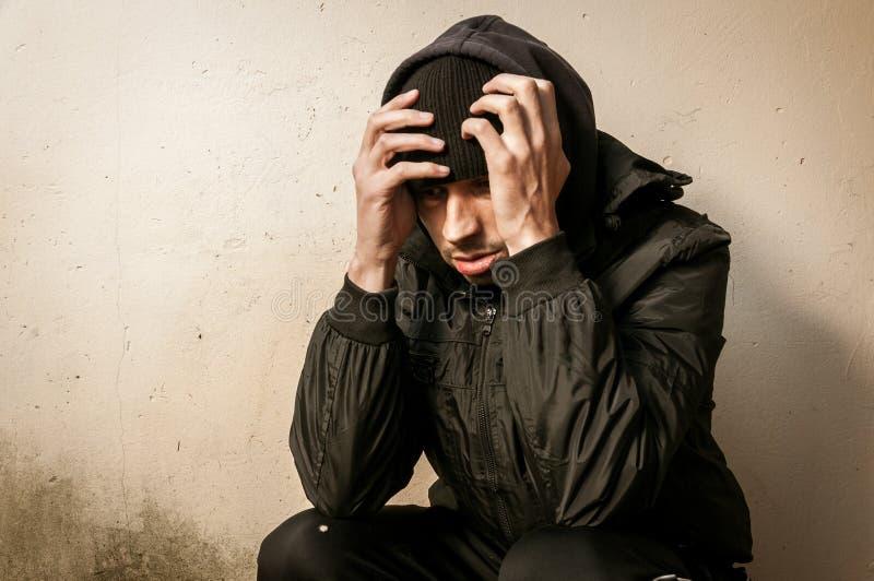无家可归的人药物和酒精上瘾者单独坐和沮丧在偏僻街道的感觉急切和在寒冷冬天天, 图库摄影