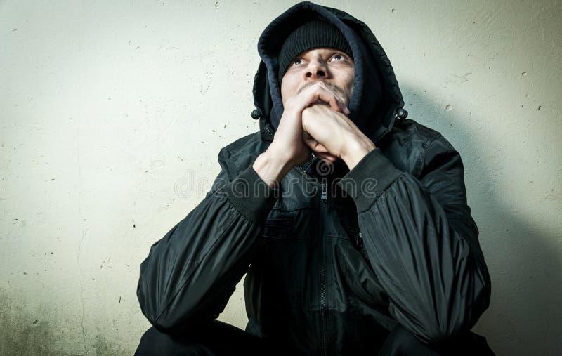 无家可归的人药物和酒精上瘾者单独坐和沮丧在感觉急切冷的冬季衣服的街道和孤独, 库存图片