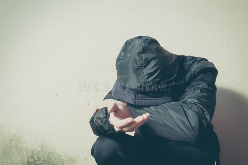 无家可归的叫化子人药物和酒精上瘾者单独坐和沮丧在感觉急切寒冷和l的冬季衣服的街道 免版税库存图片