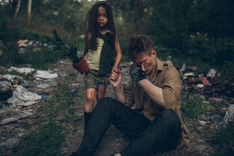 无家可归的哭泣的父亲和女儿是在垃圾堆 库存图片
