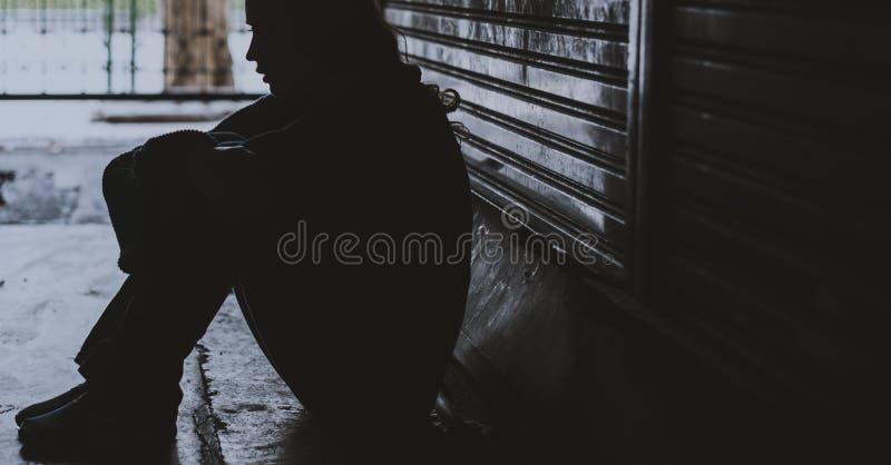 无家可归的妇女坐绝望街道的边 免版税库存照片