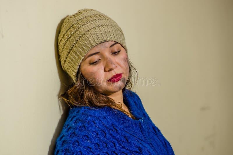 无家可归的妇女画象在街道上的在穿一蓝色有冠乌鸦的冷的秋天天气在边路 免版税库存图片
