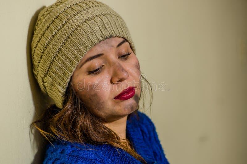 无家可归的妇女画象在街道上的在穿一蓝色有冠乌鸦的冷的秋天天气在边路 库存照片