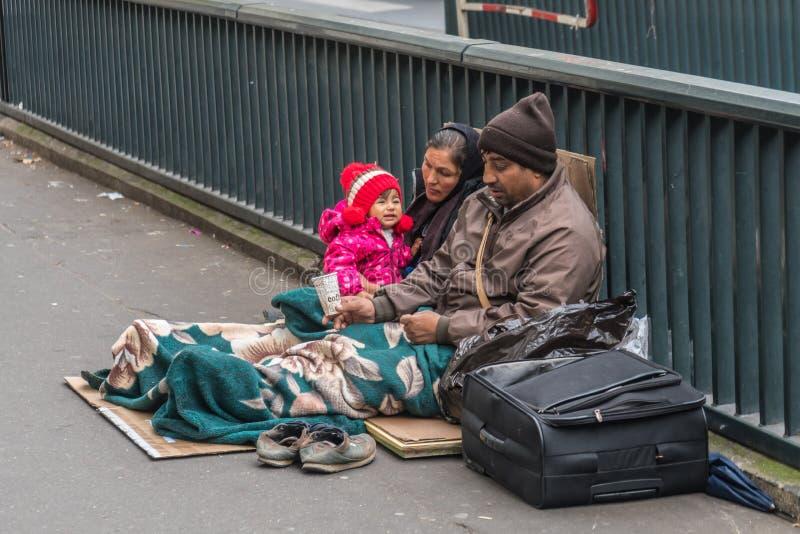 无家可归的家庭坐街道 免版税库存照片
