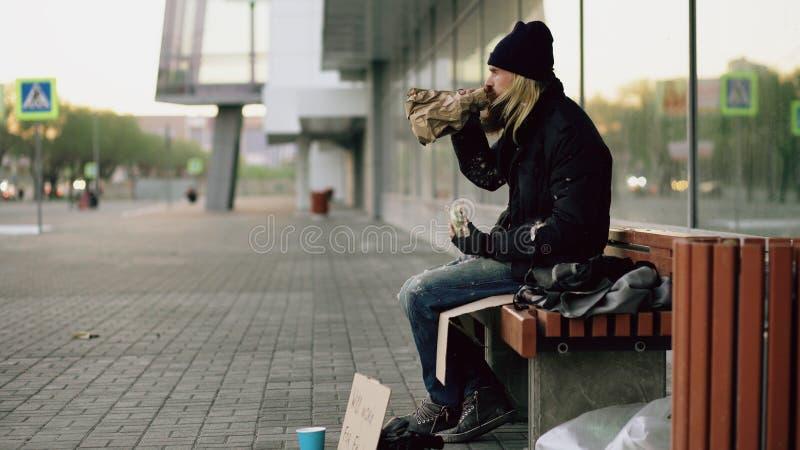 无家可归的年轻食人的三明治和饮用的酒精从纸袋在长凳在城市街道在晚上 库存图片