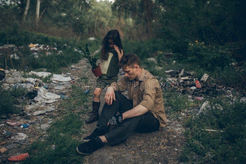 无家可归的父亲和他哭泣的女儿是在垃圾堆 免版税库存图片