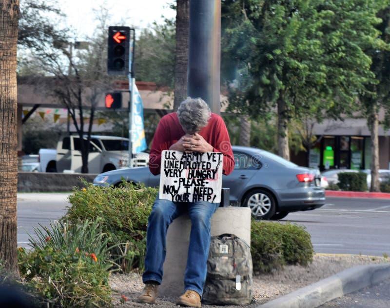 无家可归的美国陆军退伍军人坐在Mesa的一个角落,亚利桑那 免版税库存照片