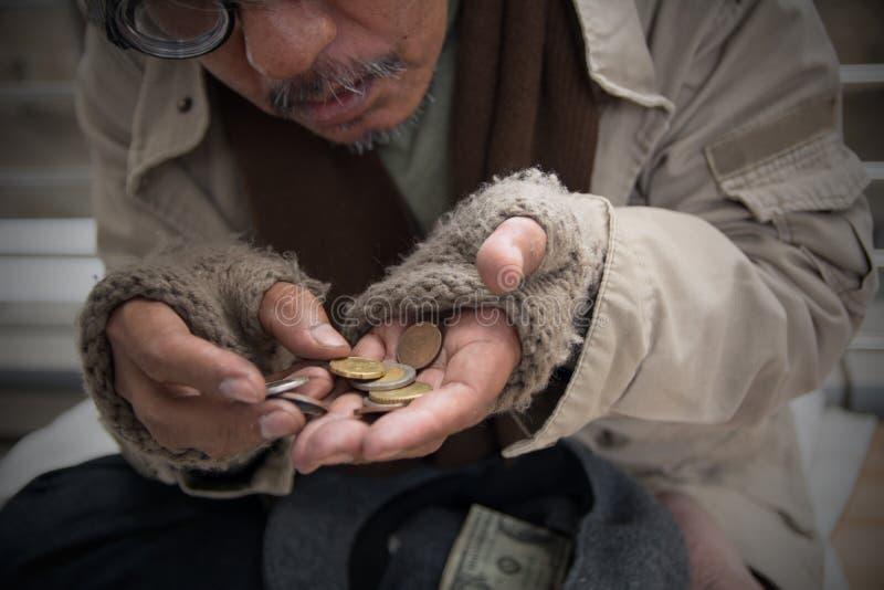 无家可归的资深成人人坐和乞求在天桥 免版税库存照片