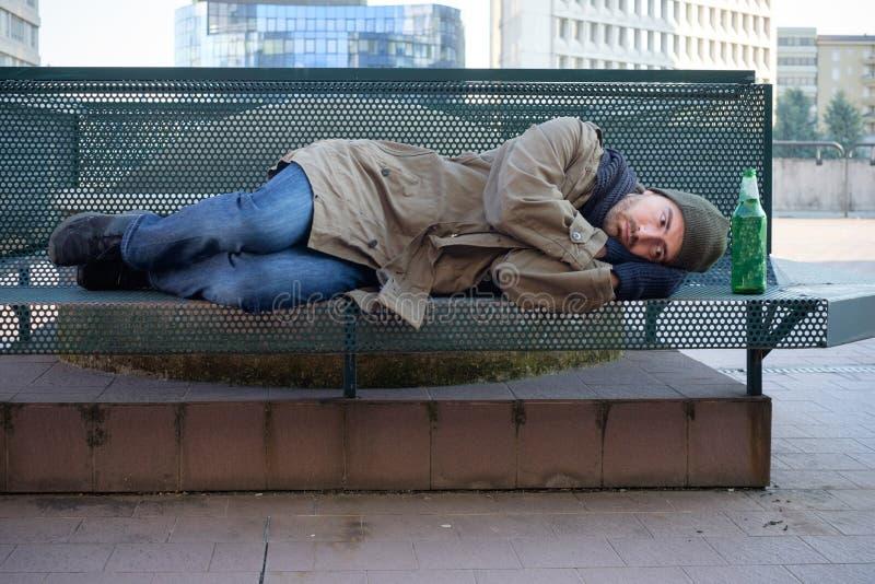 无家可归睡觉在寒冷的长凳 免版税库存照片