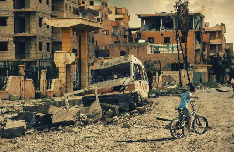 无家可归者小男孩骑马自行车在被毁坏的城市、军用战士和直升机和坦克 免版税图库摄影