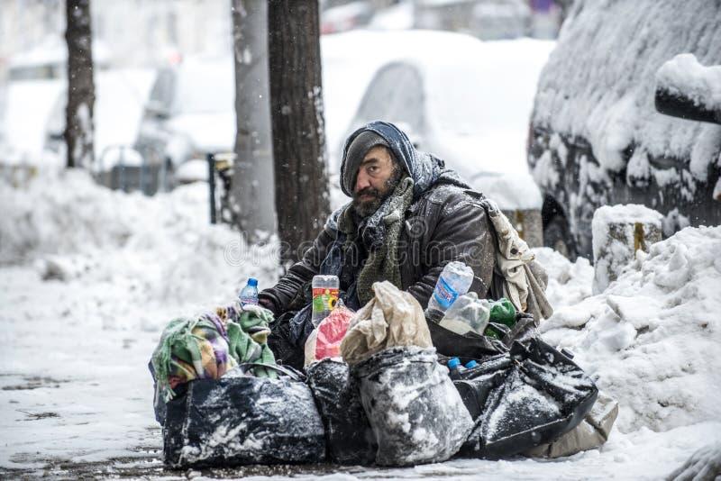 无家可归者,流浪汉在雪坐街道在索非亚,保加利亚的中心 免版税库存图片