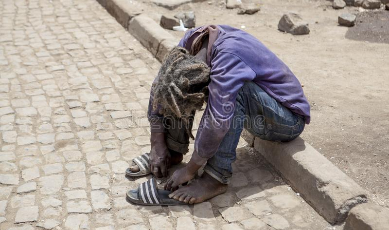 无家可归者,流浪汉 一个肮脏的有臭味的流浪者人是坐外部和哭泣充满哀情 免版税库存照片