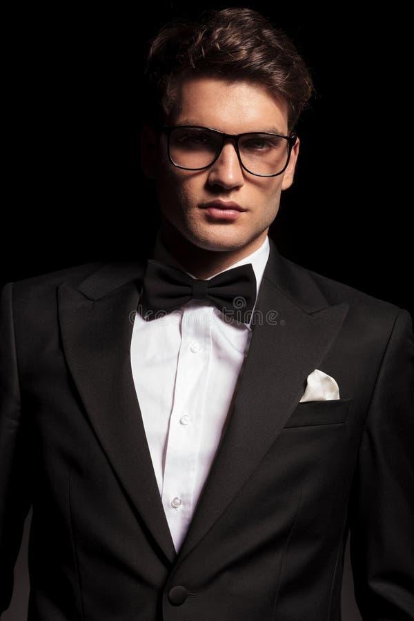 戴无尾礼服和眼镜的典雅的年轻人 库存图片