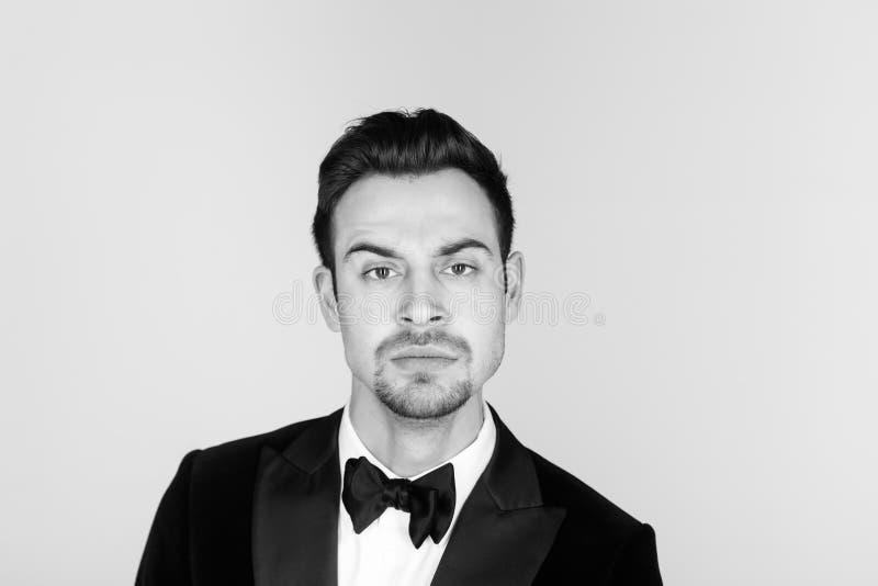 无尾礼服的年轻英俊的人,严重看照相机 图库摄影