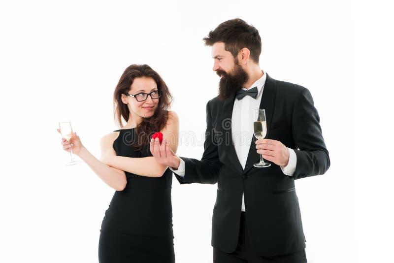 无尾礼服的愉快的人对提案做性感的妇女 在爱的夫妇庆祝订婚用香槟 婚礼很快是 ? 库存照片