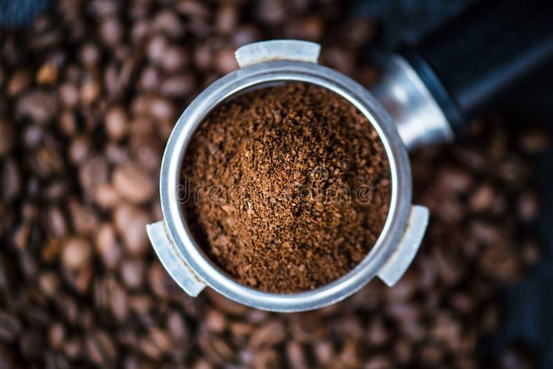 无底的过滤器用在一张木黑桌上的研磨豆 烤的豆咖啡 浓咖啡咖啡提取 准备浓咖啡 免版税图库摄影