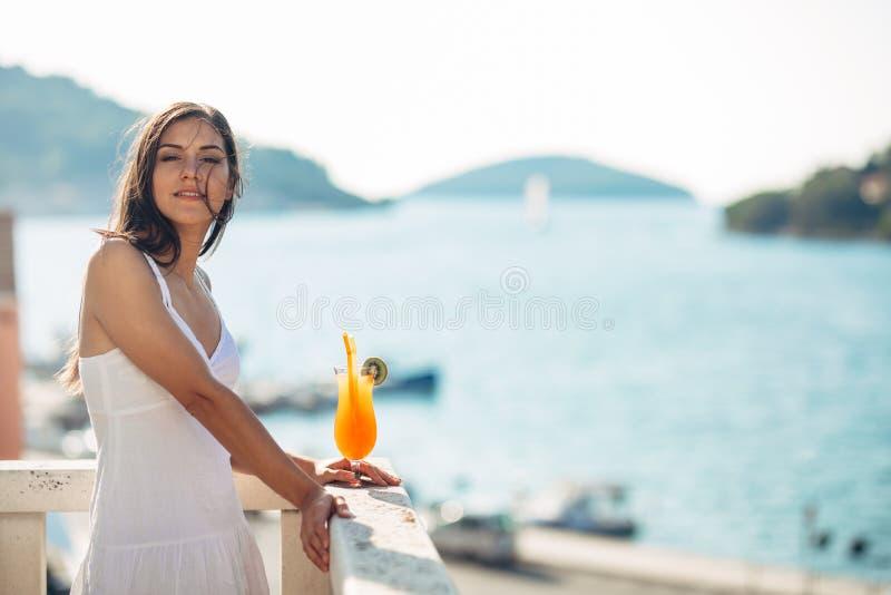 无忧无虑的年轻女性在假日获得的暑假乐趣在一个晴天,放松有海景,听挥动 库存照片