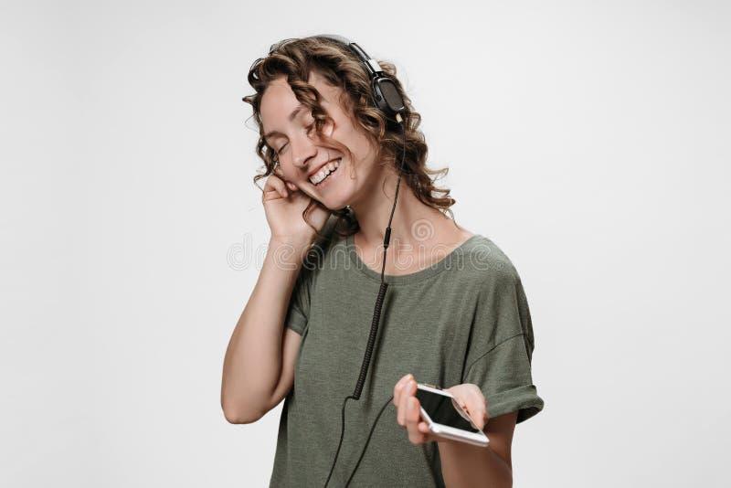 无忧无虑的快乐的年轻卷曲妇女听与她的现代立体声耳机的喜爱的音乐 免版税库存图片