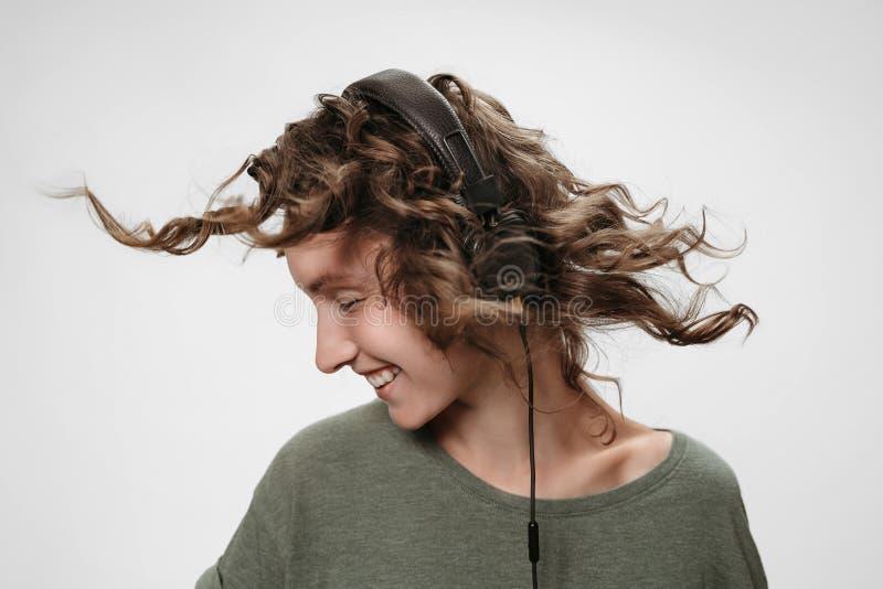 无忧无虑的快乐的年轻卷曲妇女听喜爱的音乐 免版税库存照片