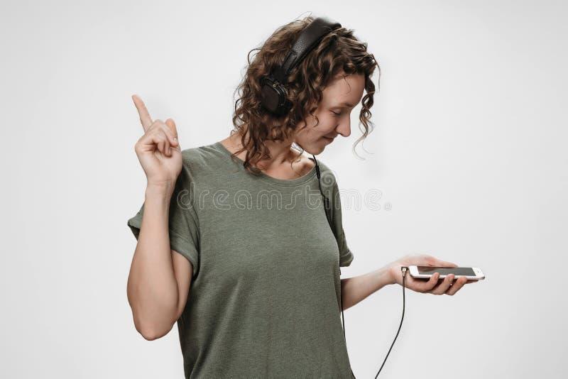 无忧无虑的快乐的年轻卷曲妇女听在音乐应用程序的喜爱的播放表 免版税库存照片