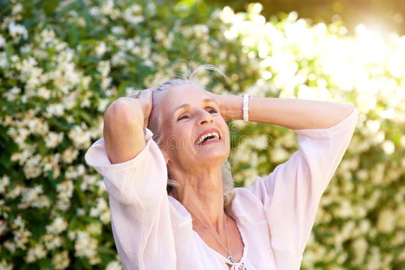 无忧无虑的老妇人用在头发的手 免版税库存照片